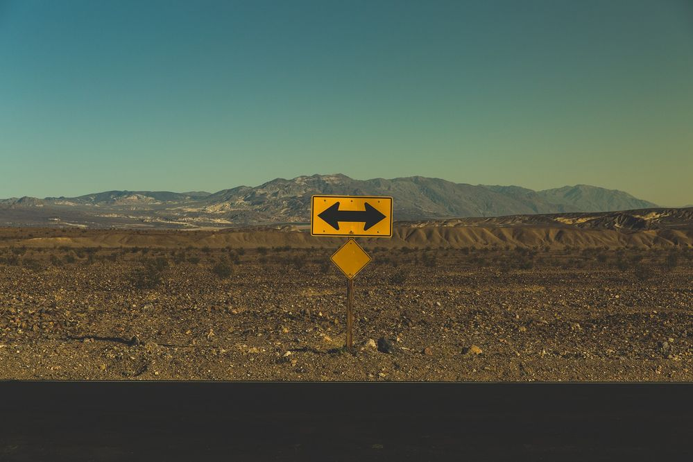 Photo of a sign with an arrow pointing in two directions